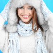 Stock Photo: Beautiful smiling girl in hat and mittens on blue background