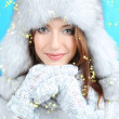 Beautiful smiling girl in hat and mittens on blue background — Stock Photo #36123953