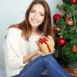 Beautiful girl near Christmas tree with gift — Lizenzfreies Foto
