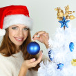Beautiful smiling girl near Christmas tree with ball — Stok fotoğraf