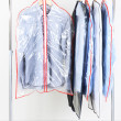 Stock Photo: Office male clothes in cases for storing on hangers, on gray background