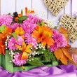 Flowers composition in crate with decorations on table on wooden background — Stock Photo #36125689