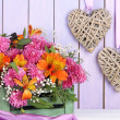 Flowers composition in crate with decorative hearts on table on wooden background — Stock Photo