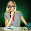 Stock Photo: Wicked chemistry teacher sitting at table on dark colorful background
