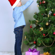 Little boy decorating Christmas tree with baubles in room — Stock Photo #36127107