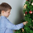 Little boy decorating Christmas tree with baubles in room — Stock Photo #36127139