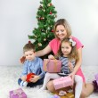 Nice mother and her children with gifts near decorating Christmas tree in room — Stock Photo