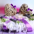 Decorative wreath with candles and wicker heats on table on bright background — Stock Photo