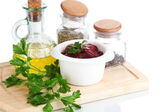 Raw liver in bowl with spices and condiments isolated on white — Stock Photo