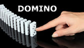 Hand pushing dominoes isolated on black — Stock Photo