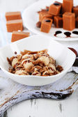 Many toffee on plate and in bowl on napkin on board close-up — Stock Photo