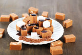 Many toffee and sugar cubes on plate on wooden table — Stock Photo