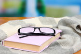 Composition with old book, eye glasses and plaid on bright background — Stock Photo