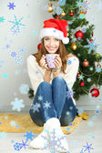 Beautiful smiling girl sitting near Christmas tree with cup — Stock Photo