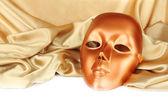 Mask on gold fabric on white background — Stock Photo