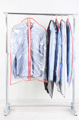 Office male clothes in cases for storing on hangers, on gray background — Stock Photo