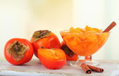 Ripe persimmons with jam in glass saucer and cinnamon on table on bright background — Stock Photo