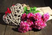 ピンクの菊の手紙と木製のテーブルで心の花束 — ストック写真
