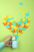Paper butterflies fly out of teapot on green wall background — Stock Photo