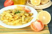 Ruddy fried potatoes on plate on tablecloth close-up — Foto Stock