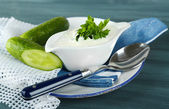Cucumber yogurt in sauceboat, on color napkin, oncolor wooden background — Photo