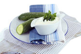 Cucumber yogurt in sauceboat, on color napkin, isolated on white — Stock Photo