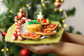 Hands holding plate with homemade cookies and candies, on bright background — Stock Photo