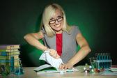 Professeur de chimie méchants assis à table sur fond coloré foncé — Photo