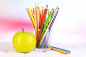 Colorful pencils in glass on wooden table on bright background — Stock Photo