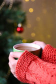 Hands holding mug of hot drink, close-up, on Christmas tree background — Stock Photo