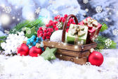 Composition with Christmas decorations in basket, fir tree on light background — Стоковое фото
