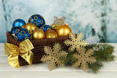 Christmas decorations in basket and spruce branches on table on bright background — Foto Stock