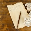 Crumpled paper balls with ink pen and music sheet on wooden background — Stock fotografie