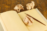 Crumpled paper balls with notebook and ink pen on wooden background — Zdjęcie stockowe