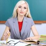 School teacher verifies homework on blackboard background — Stock Photo #36235845