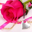 Beautiful pink rose with heart pendant — Stock Photo #36231439