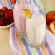 Delicious milk shakes with strawberries and peach on wooden table close-up — Stock Photo
