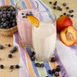 Delicious milk shakes with blackberry and peach on wooden table close-up — Stock Photo