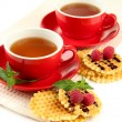 Cups of tea with cookies and raspberries isolated on white — Stock Photo