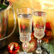 Composition with Christmas decorations and two champagne glasses, on bright background — Stock Photo #36232649