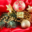 Beautiful Christmas decor on red satin cloth — Stock Photo #36233687
