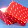 Gift box with bright light on it on blue background — Stock Photo