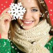 Beautiful smiling girl with Christmas snowflake on red background — ストック写真