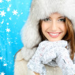 Beautiful smiling girl in hat and mittens on blue background — Stock Photo