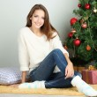 Beautiful smiling girl sitting near Christmas tree in room — Stock Photo #36235173
