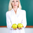 School teacher near blackboard with apples in classroom  — Stock Photo