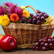 Composition with beautiful flowers in wicker basket and fruits, on bright background — Stock Photo #36236497