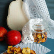 Dried apples in glass jar, on color wooden background — Stockfoto