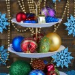 Christmas decorations on dessert stand, on  color wooden background — Stock fotografie