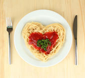 Cooked spaghetti carefully arranged in heart shape and topped with tomato sauce, on wooden background — Stock Photo